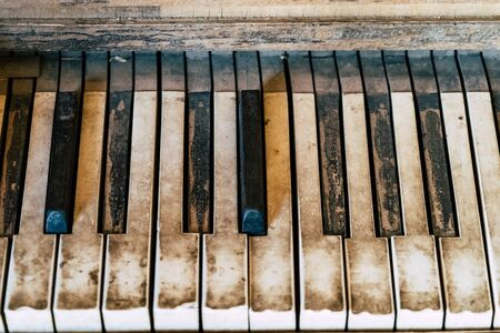 Close up of dirty, old rustic antique piano keys. Useful for backgrounds and headers