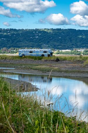 Old retro abandoned bus sits along in a marsh along the Homer Spit in the Kachemak Bay area of Alaska. Reflection of the vehicle in the pond Stock Photo - 139025521