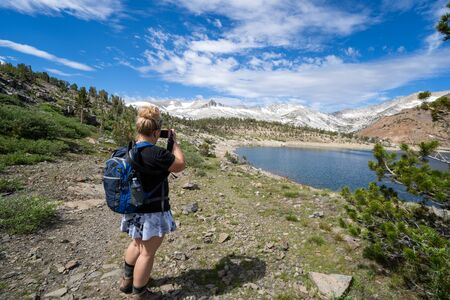 Young blonde female hiker takes photos of an alpine lake in California