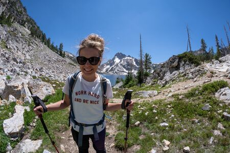 Woman hiker stands on the trail of Sawtooth Lake in Idaho's Sawtooth Mountain Range in the Salmon-Challis National Forest near Stanley Idaho.