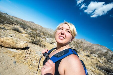 Female blonde hiker spots to squit to look off into the distance as she hikes through the California desert in the Coachella Valley Stock Photo