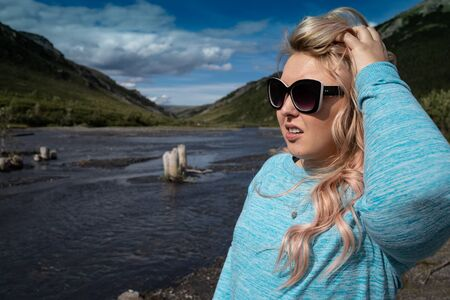 Blonde female stands near the Savage River in Denali National Park, posing and looking at the Alaskan scenery