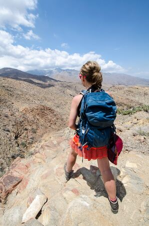 A female hiker, hiking in the Indian Canyons in Palm Springs California, stops to admire the mountain and desert view. Banco de Imagens