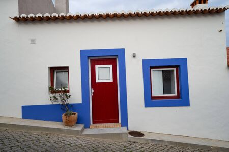 Cobblestone street with blue and white traditional colorful homes and buildings in the Algarve town of Odeceixe