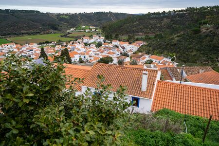 Overlook from a hill, looking over the rooftops of houses and buildings of Odeceixe, Portugal, a town in the Algarve