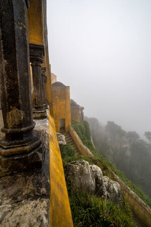 View of the side of the Pena Palace castle in Sintra, on a very foggy day with poor visibility of the landscape below