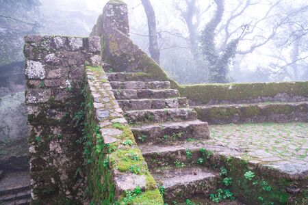 Moss covered old steps and stairs of the Moorish Castle (Castle of Moors) on a foggy, misty day in Sintra Portugal