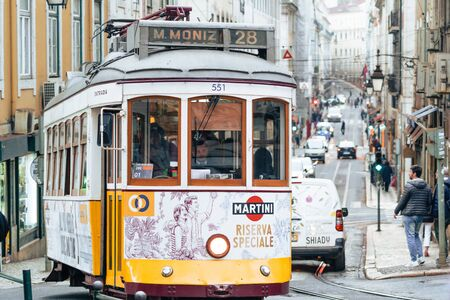 Lisbon, Portugal - January 17, 2020: Street car 28, the famous yellow tourist tram, makes its way up the narrow, steep streets of the downtown area