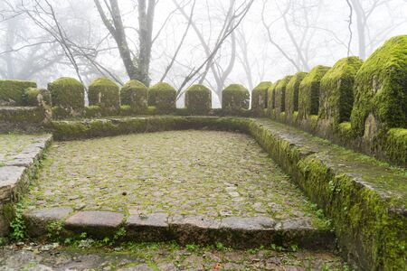 Moss covered walls of the Moorish Castle (Castle of Moors) on a foggy, misty day in Sintra Portugal