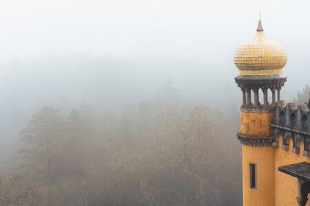 Detail view of a yellow dome column at Pena Palace (Palacio da Pena) fully engulfed in fog with poor views of the nearby forest
