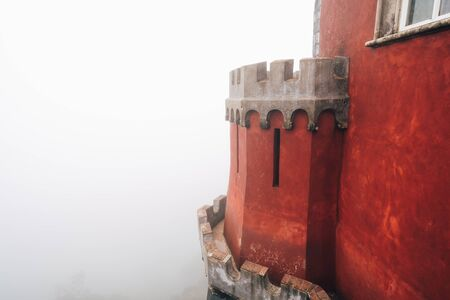 Detail view of a red dome column at Pena Palace (Palacio da Pena) fully engulfed in fog with poor views of the nearby forest