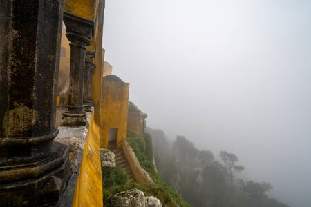 View of the side of the Pena Palace castle in Sintra, on a very foggy day with poor visibility of the landscape below Stock Photo - 139041979
