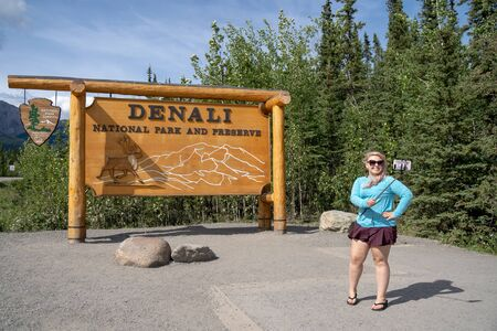 AUGUST 1 2018 - DENALI NATIONAL PARK ALASKA: A blonde tourist woman uses a selfie stick to take a photo with her smartphone of the park entrance sign