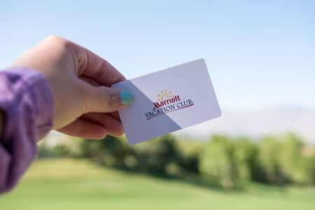 MAY 8 2018 - PALM DESERT, CALIFORNIA: A female hand holds a Marriott Vacation Club room card key on a sunny day. Marriott Vacation club is the hotel chains timeshare business unit. Selective focus