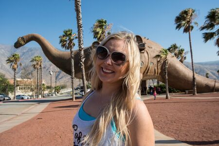 JUNE 30 2017 - CABAZON, CALIFORNIA: Adult female stands by a giant brontosaurus dinosaur statue on a bright sunny summer day. Cabazon Dinosaurs are a popular roadside attraction Stock Photo - 139042012
