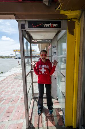 MAY 8 2016 - CABAZON, CALIFORNIA: An adult female stands inside of an abandoned telephone booth, looking surprised that there is no phone