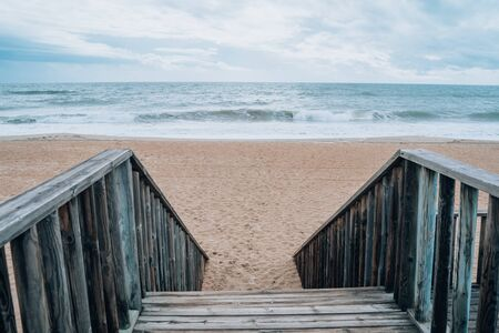 Stairs leading down to the sandy beach at Islantilla Spain during a cloudy, cold winter day