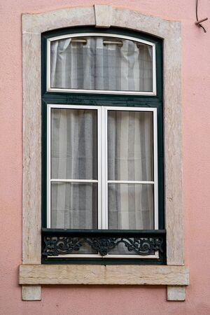 Pretty pink window in portrait orientation in Lisbon, Portugal, typical of the architecture of the area