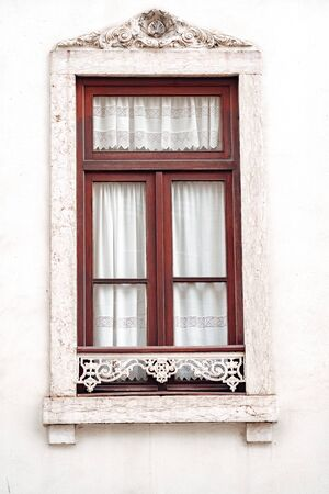 Ornate window with white moulding and lace curtains, typical of the architecture of Lisbon, Portugal Stock Photo - 139102100