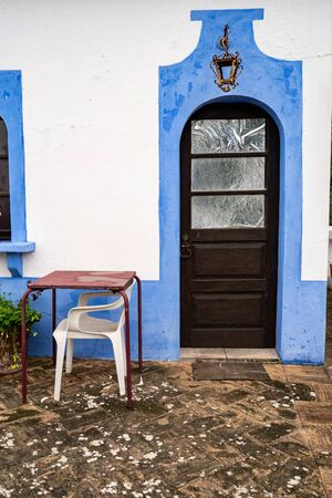 Colorful blue wall facade, door, and table and chairs in the small village of Alte, Portugal