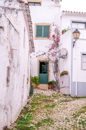 Cute alley with cobblestones and colorful doorways and white walls in the small village of Alte, Portugal