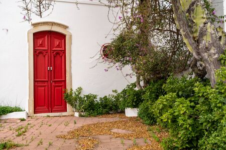 Adorable red doorway with landscaping, trees, and flowers against a white wall in Alte, Portugal