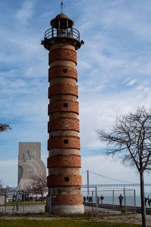 Lisbon, Portugal - January 17, 2020: Old brick lighthouse, with the Monument to the Discoveries in the background in the Belem area Stock Photo