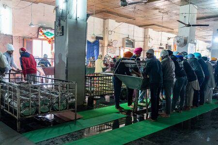 Amritsar India - Febuary 8, 2020: Volunteers wash dishes at the kitchen (Langar) at the Sikh Golden Temple (sri harmandir sahib)