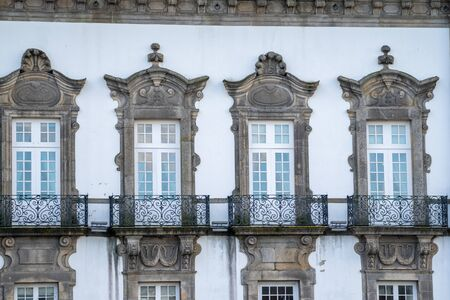 Traditional Porto Portugal building exterior with windows and ornate balconies with a white facade