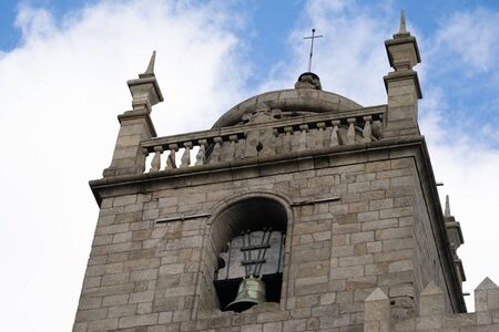 The Porto Cathedral bell tower close up, detail view against a blue sky with clouds in Portugal