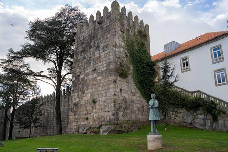 Porto, Portugal - January 20, 2020: The Muralha Primitiva (Primitive Wall) building remains and statue of Arnaldo Gama