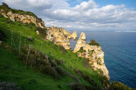 Steep, sloped natural cliff formations of Algarve coastline with green grass at Ponta da Piedade, in Algarve Portugal 版權商用圖片