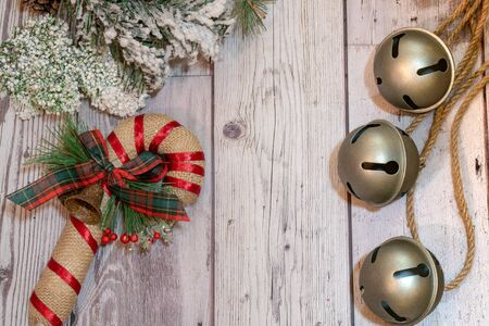 Jingle bells on rope with decorative flocked snow pine branches and a burlap candy cane. Wood background, copy space included
