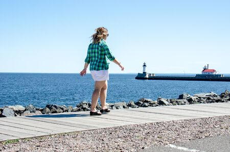 Adult female takes a relaxing stroll on Duluth Canal Park Lakewalk along Lake Superior. Lighthouses in background