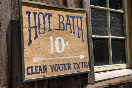 Funny sign for a Hot Bath Clean Water Extra for 10 cents on a rustic wooden abandoned building 版權商用圖片