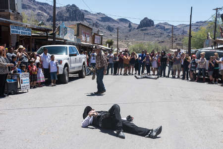 MAY 20 2017 - OATMAN, ARIZONA: Actors portray an old west outlaw shootout at Noon, dramatized for tourists, on a warm spring day. The fake bank robber lies on the ground, pretending to be shot dead.