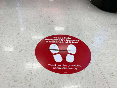 Eau Claire, Wisconsin - March 30, 2020: Sign on the floor of a Target store reminding customers to practice social distancing during the Coronavirus pandemic outbreak to prevent virus from spreading