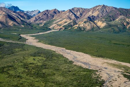 Beautiful colorful view of Polychrome Pass and a braided winding river going through the Alaska Range mountains in Denali National Park on a sunny day Imagens