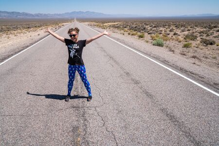 Adult woman stands with arms raised in the middle of the road (Extraterrestrial Highway in Nevada's desert). Concept for daring, daredevil, dare, open road Banque d'images