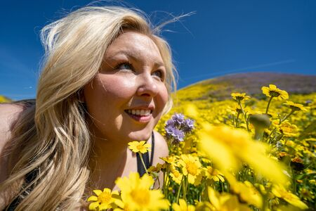 Beautiful blond woman in a yellow wildflower field, looking up at a blue sky in spring. Taken at Carrizo Plain National Monument during the California superbloom