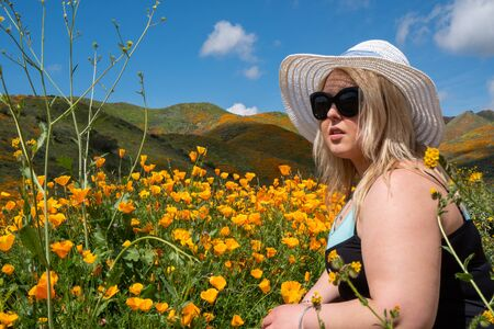 Blonde woman wearing a straw bonnet hat looks out to the field of poppy wildflowers during the superbloom