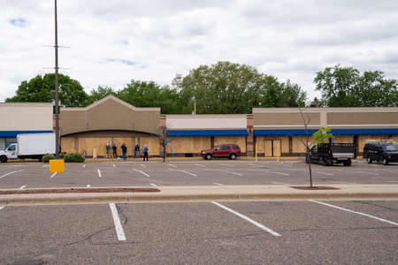 Minneapolis, Minnesota - May 29, 2020: Work crews board up buildings in a strip mall with plywood, to prevent potentional looting and riot damage in the death of George Floyd by police