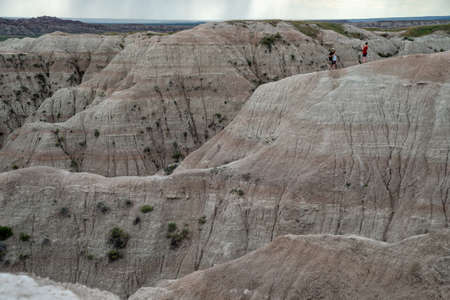 Badlands National Park, South Dakota - June 21, 2020: Tourists pose for photos while standing on a dangerous cliff