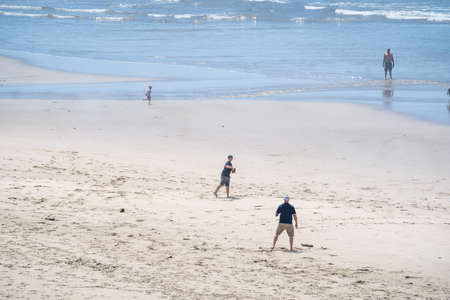Newport, Oregon - August 1, 2020: Father and son playing catch on the beach in Newport Oregon in the summer