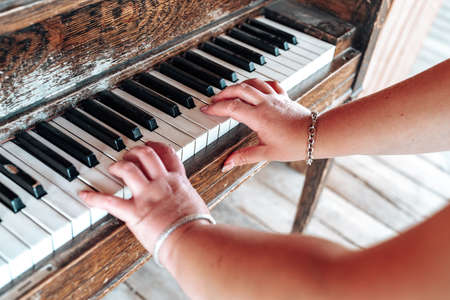 Female plays an old rustic piano, only arms and fingers shown. Selective focus on right hand