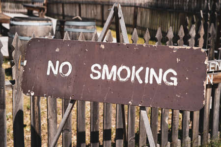 Wooden No Smoking sign posted to a fence 版權商用圖片