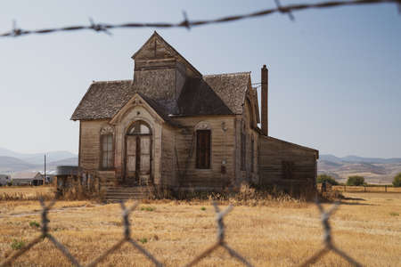 Old, abandoned LDS mormon church, framed by barbed wire, in Ovid, Idaho
