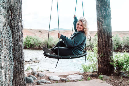 Happy, relaxed blonde woman sits on a tree swing near a river, looking happy 免版税图像
