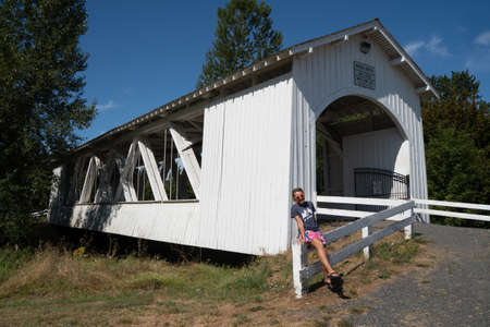 Sweet Home, Oregon - August 2, 2020: Adult woman poses on the fence near the Weddle covered bridge