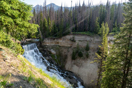 Brooks Falls waterfall in the Shoshone National Forest in Wyoming, Sunbeams lens flare in photo